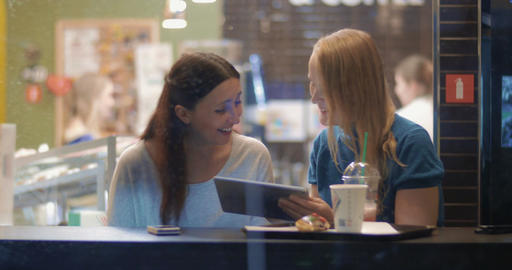 Female friends talking and using touch pad in cafe Footage