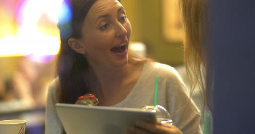 Women friends using tablet PC and eating cake in cafe Footage