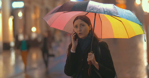 Brunette woman talks on the phone on the street on rainy day Footage