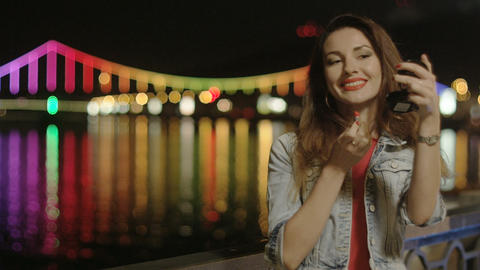 Woman Putting Red Lipstick Outside At Night City Lights Refelecting In The Water stock footage