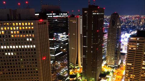 Tokyo shinjuku Skyscrapers dominate frame, and lights grow bright as night falls Footage