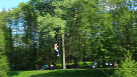 a girl is riding a bungee ride in the park Footage