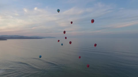 Chinese Lanterns Flying In The Air Over The Ocean And Mountains. On The Sunset stock footage