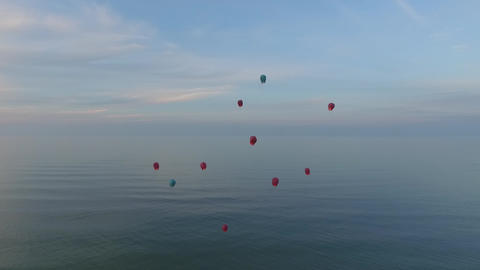 Chinese lanterns flying in the air over the ocean and mountains. On the Sunset Footage