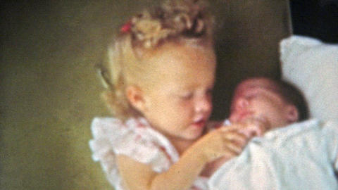 1951: Big sister holding baby brother kisses him on the head Footage