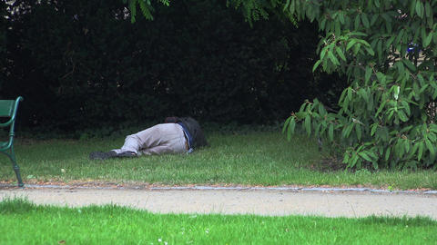 Homeless bum sleeping on the grass. 4K Footage