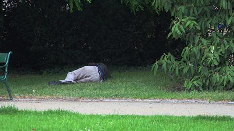 Homeless bum sleeping on the grass. 4K Footage