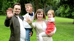 family (middle couple in love, cute girl and small boy) together waving hands in Footage