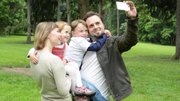 family (middle couple in love, cute girl and small boy) take a photo with smartp Footage