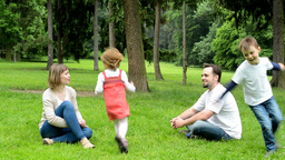 family (middle couple in love, cute girl and small boy) relax together in park - Footage