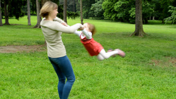 Mother rotate with daughter (cute girl) around - park Footage