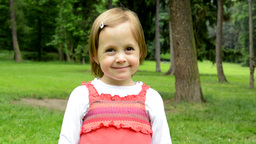 little cute girl smiles to camera - park in background - park Footage
