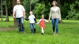 family (middle couple in love, cute girl and small boy) walking in park from dis Footage