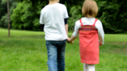 children (siblings - boy and girl) holding hands and walking in park Footage
