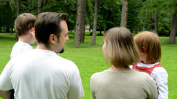 family (middle aged couple in love, boy and girl) relax in park and point to dis Footage