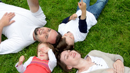 family (middle aged couple in love, boy and girl) lying in grass and talk Footage