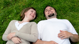 middle aged couple in love lying in grass and talk Footage