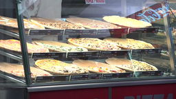 street stand with pizza - closeup - walking people - night city Footage