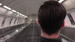 young handsome hipster man travels on the escalator in the subway - shot from ba Footage