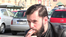 young handsome hipster man smokes a cigarette on the street - parked cars in the Footage