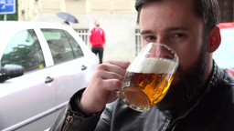 young handsome hipster man drinks beer in the restaurant and smiles to camera -  Footage