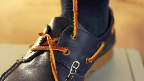 YOUNG MAN TO TIE THE LACES IN SHOES Footage