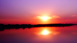 Beautiful sunset with flying birds on the lake and sun reflections Footage