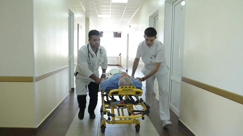 Two doctors carry a patient on stretcher Footage