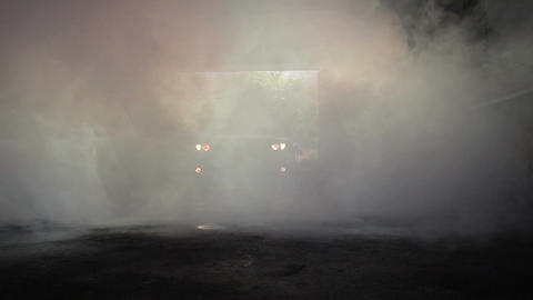 The car enters the dark, smoke-filled garage with its lights on Footage