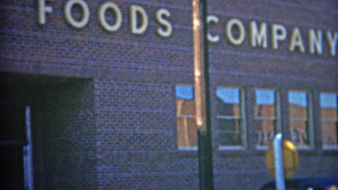 1953: Kraft foods company enterance where two workers emerge Footage