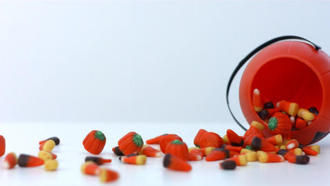 candy corn spills out of a pumpkin container in slow motion Footage