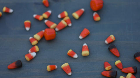 candy corn for halloween slides across a wood background in slow motion Live Action