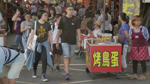 Shoppers walking through Danshui market entrance side Footage