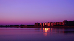 Urban landscape with lake at sunset. Citiscape at dusk with golden reflections Footage