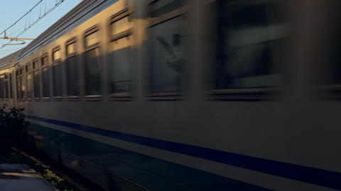 Passenger Train Passing A Station At High Speed stock footage