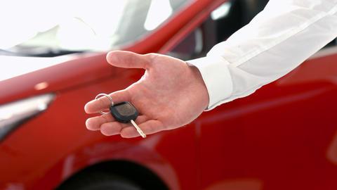 Businessman holding out car keys Live Action