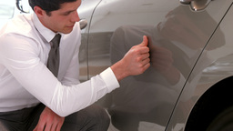 businessman checking the cars paint job Footage
