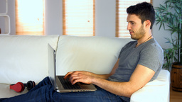 Man using his laptop on the couch Footage