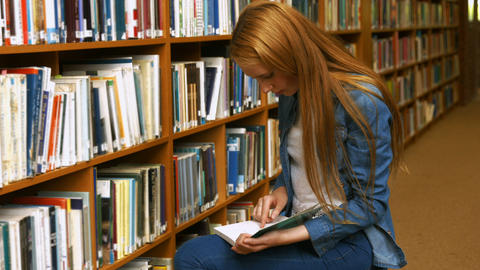 Student reading a book in the library Footage