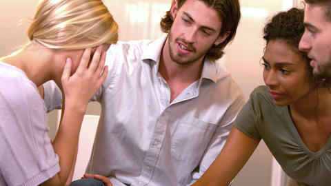Stressed out woman being comforted by coworkers Footage