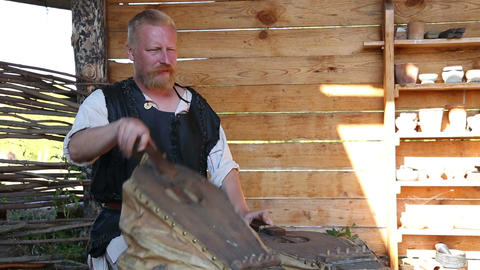 The blacksmith's assistant is working the bellows Footage