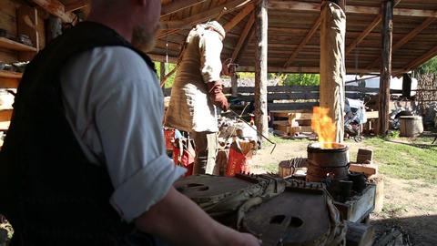Blacksmith with assistant work in the forge Footage