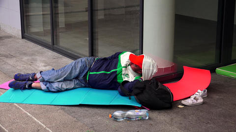 Emigrant, a refugee, sleeping on the street at the train station in Budapest. 4K Footage