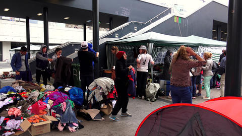 Immigrants and refugees dismantled clothes and warm clothes at the railway stati Footage