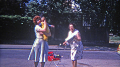 MONTREAL, CANADA 1973: Fashionable French Canadian mom taking baby from oldnanny Footage