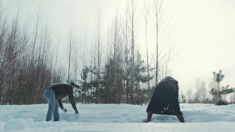 Young couple playing outdoors in the snow, slowmotion Footage