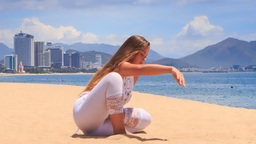 girl in white lace costume demonstrates yoga asana child's pose on beach Footage