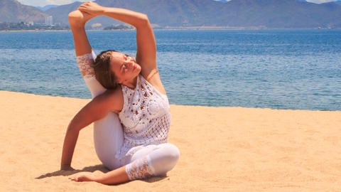 girl in white lace costume shows yoga asana leg behind head on beach Footage