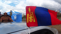small Mongolian flag flies over the car on the background of the statue of Gengh Footage
