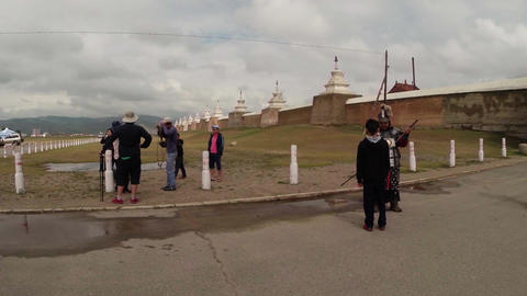 Mongolian warrior in armor with tourists around the ancient walls of a Buddhist  Footage